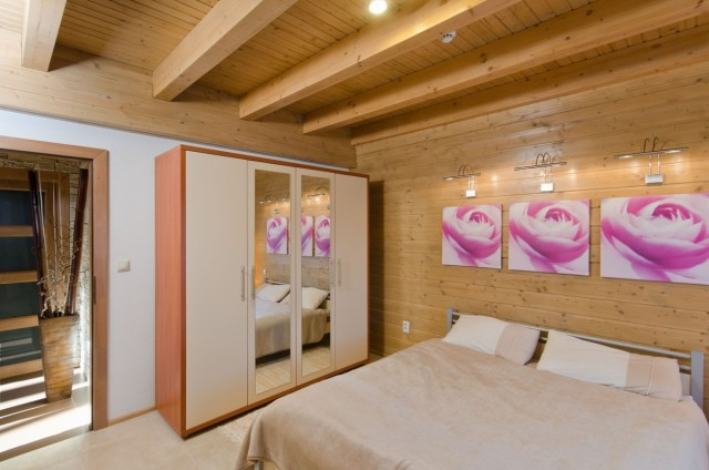 Ložnice v přízemí luxusního srubu